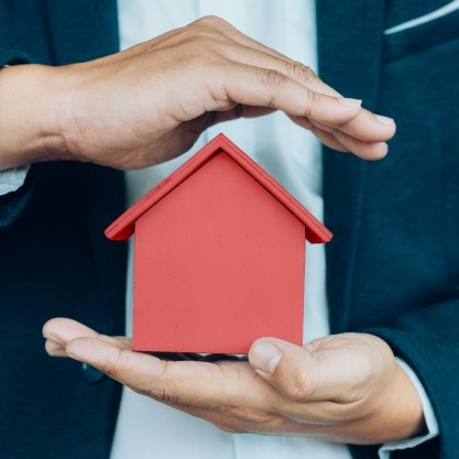 business-man-hand-hold-house-model-saving-small-house_1421-86